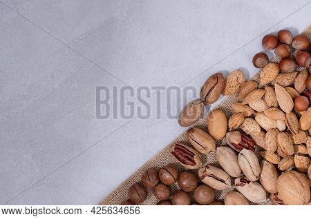 A Scattering Of Unpeeled Nuts On A Jute Fabric On A Light Background With Copy Space. Assortment Of