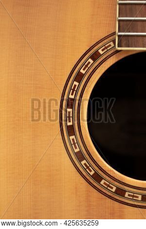 Old Wood Guitar Without Strings Made Of Light Wood With Brown Patterns And A Black Hole