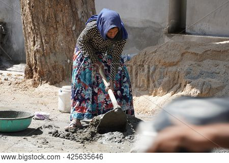 An Indian Woman Worker Is Working Her Heavy Labor Day Job At The Construction Site. She Is Mixing Ce