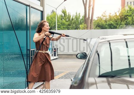 Side View Young Adult Woman Washing Car With High Pressure Water Equipment Pump Self-service Outdoor