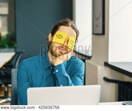 Low Energy Level. Tired Sleeping Young Male Office Worker Hiding Eyes With Funny Sticky Notes, Compa