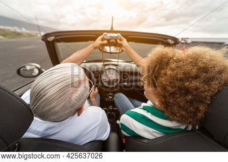 Happy Senior Couple Having Fun Taking Photo With Old Vintage Camera While Driving On New Convertible