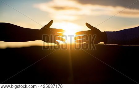 Two Hands Silhouette On Sky Background, Connection Or Help Concept. Outstretched Hands, Salvation, H