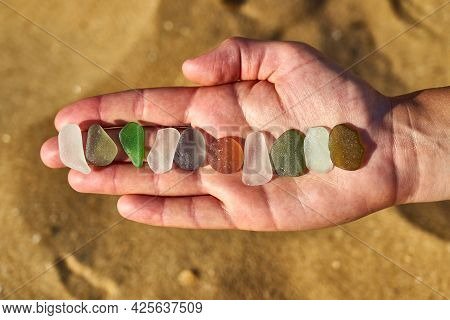 Different Colours Of Sea Glass Collected From A Beach Are Laid Out In A Line On A Person's Hand. A P