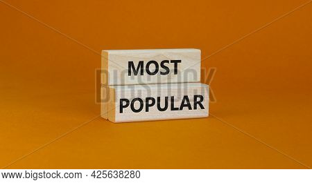 Most Popular Symbol. Concept Words Most Popular On Wooden Blocks On A Beautiful Orange Background. C