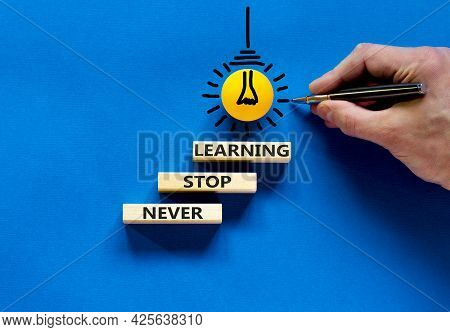 Never Stop Learning Symbol. Wooden Blocks With Concept Words Never Stop Learning. Blue Background. B