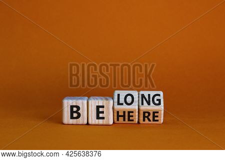 Be Here Belong Symbol. Turned Cubes And Changed Words 'be Here' To 'belong'. Beautiful Orange Backgr