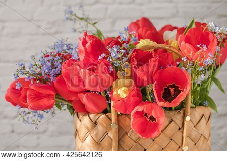 Summer Or Spring Bouquet Of Daffodils And Red Tulips In A Wicker Basket Located On A White Backgroun