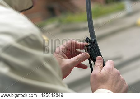 Man Holds The Latch On The Wiper Blade Holder With His Fingers On A Blurry Background