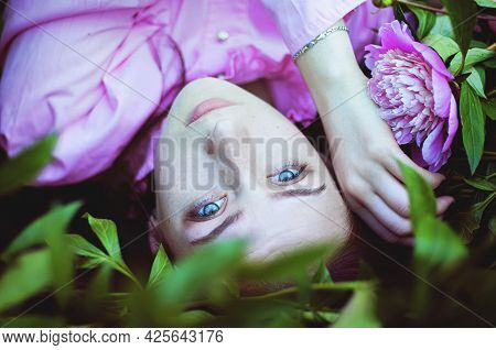 Portrait Of Young Attractive Woman In Pink Dress In Spring Garden With Blooming Pink Peonies. Spring