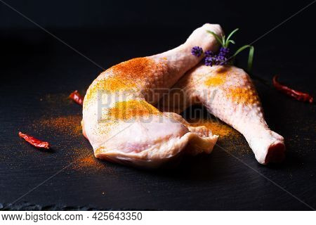 Food Concept Raw Chicken Quarters With Spices On Black Slate Stone Board With Copy Space