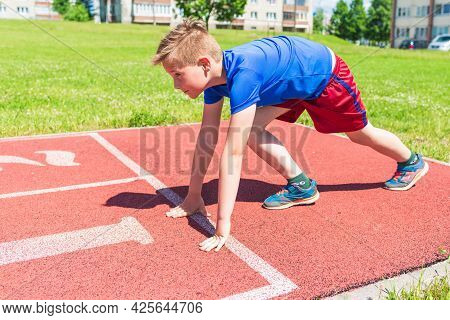 Caucasian Schoolboy Prepare To Start Running On A Red Track.young Boy In Starting Position Ready For