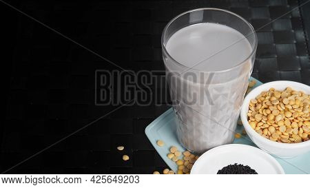 Soy Milk Blended With Black Sesame In Clear Glass On Black Plate Mat.