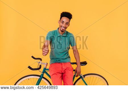 Good-humoured Male Cyclist Posing With Thumb Up. Studio Portrait Of Glad Brunette Man Posing With Bi