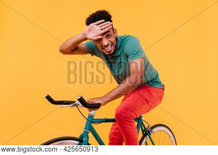Laughing Man With Curly Hairstyle Sitting On Bike. Studio Photo Of African Guy In Colorful Attire Ri