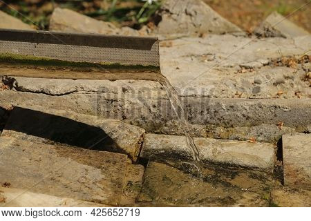 Drainpipe Made Of Iron From Which Water Flows Into A Stone Ditch In The Open Air