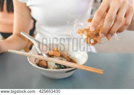 Woman In White T-shirt Eats Pork Rind Or Pork Crackling With Thai Noodle.