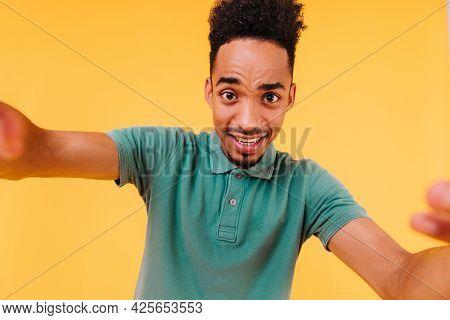 Good-humoured Dark-eyed Guy With Short Hair Making Selfie. Indoor Photo Of African Boy In Green Atti