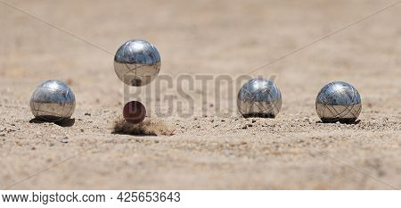 Petanque Ball Boules Bowls On A Dust Floor, Photo In Impact. Balls And A Small Wood Jack