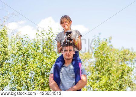 Defocused Brother Riding Sister On Back. Portrait Of Happy Girl On Man Shoulders, Piggyback. Girl Ho