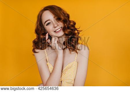 Indoor Portrait Of Lovely Red-haired Woman Enjoying Photoshoot On Yellow Background. Studio Shot Of