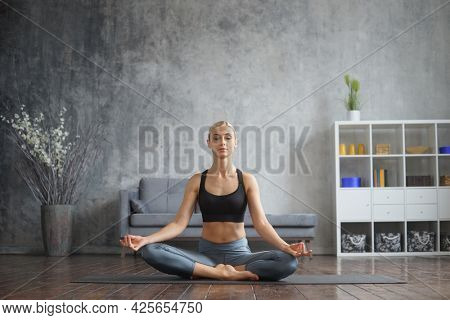 Young and sporty girl in sportswear is doing yoga exercises in home interior. Fit and slender blond woman goes in for sports and fitness. Healthcare, fat burn and wellness.