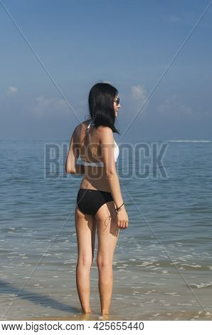 A Beautiful Chinese Woman Standing On Long Beach Looking Out At Malacca Straits At Batu Ferringhi On