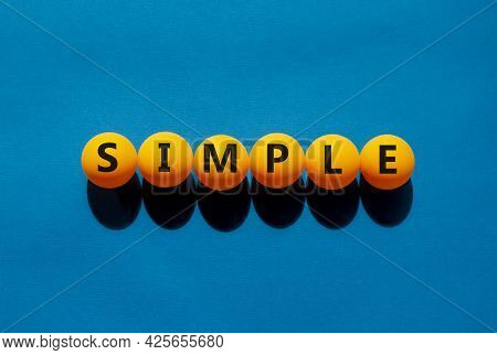 Simple And Business Symbol. The Concept Word 'simple' On Orange Table Tennis Balls On A Beautiful Bl