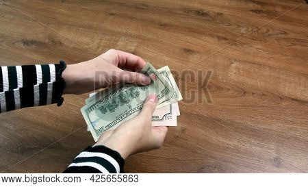Top View Female Hands Count Dollar Bills On Wood Table With Copy Space. Closeup Fifty And One Hundre