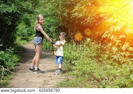 Young Beautiful Girl In Shorts Walking With Her Younger Brother In The Park In Sunset. The Little Bo