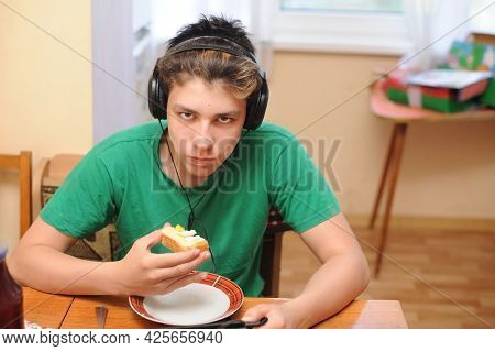 The Teenager Listens To Music In The Headphones, Sits In The Kitchen And Eats A Sandwich. He Has Ang