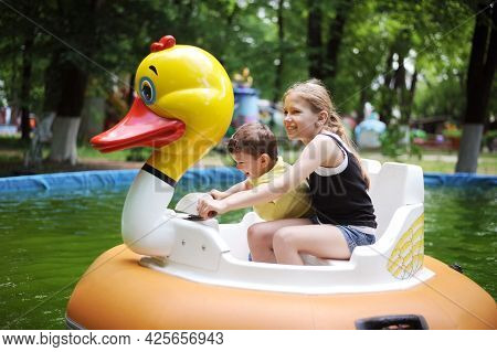 Various Children - A Little Boy And A Teenage Girl Riding On A Water Attraction In The Form Of A Lar