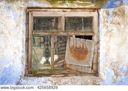 An Old Broken Window In A Dilapidated House. A Peeling Wall Of A Building With Cracks And A Broken W