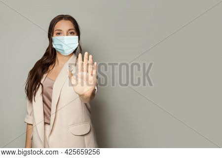 Stop Covid-19 Gesture. Woman Hand Showing Stop On Gray Background