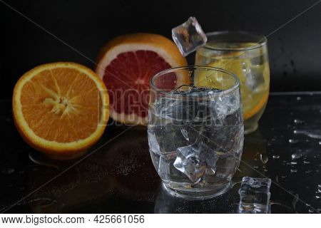 Ice Cube Flies Falls Into The Takan With Water Soda Next To Lie Orange Grapefruit And Ice On A Black