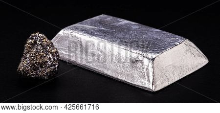 Insulated Zinc Ingot Or Bar Next To Raw Zinc Nugget On Insulated Black Background, Metal Used In The