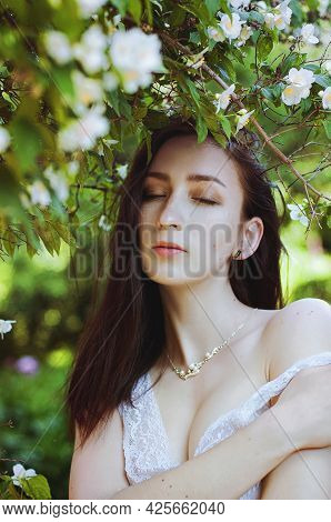 Portrait Of Young Attractive Woman In Spring Garden With Bushes Of Fragrant Jasmine. Spring Backgrou