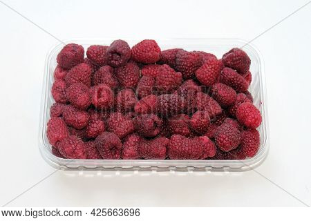 Fresh Organic Raw Raspberries Fruit Pile In Plastic Container Isolated On White Background