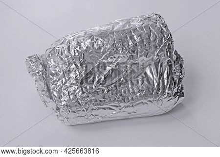 Sandwich Wrapped Up In Silver Aluminum Foil Isolated On White Background