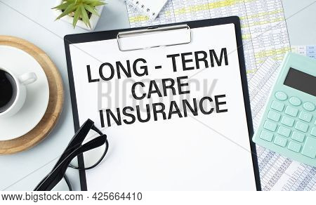 Text Long-term Care Insurance On Clipboard On Wooden Table Closeup