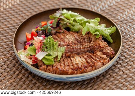 Fresh Beef Steak With Salad And Vegetables On Plate On Beach Outdoor Restaurant. Fine Dining Cuisine
