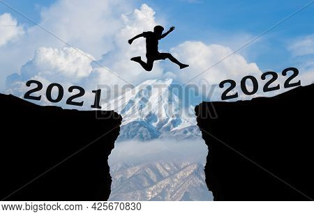 A Young Man Jump Between 2021 And 2022 Years Over The Sky And Cloud Through On The Gap Of Hill And L