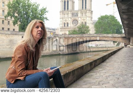 Seductive Blonde Woman Thoughtful, Sitting On A Stone Wall Along The Banks Of The Seine River, Using