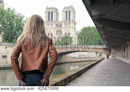 Blonde Woman In Trousers, Standing From Behind On The Banks Of The Seine. Cathedral Of Notre Dame De