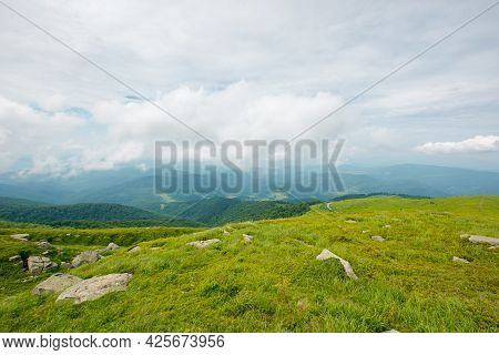 Summer Mountain Landscape. Beautiful Nature Scenery. Stones On The Grassy Hills Rolling In To The Di