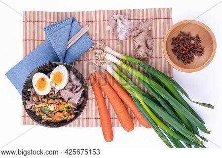 Top View Studio Shot Of Black Bowl Of Ramen Noodles With Boiled Eggs, Veggies And Turkey Meet, Ready