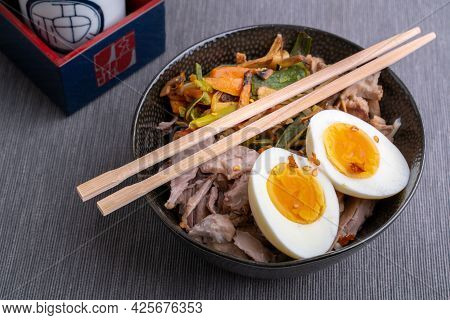 Studio Shot Of Black Bowl Of Ramen Noodles With Boiled Eggs, Veggies And Turkey Meet, Ready To Be Po
