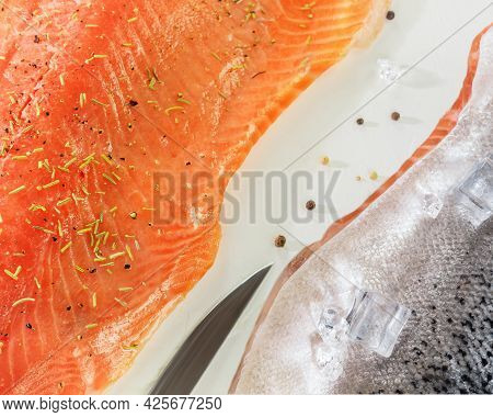 Food Horizontal Composition With Fresh Sea Fish, Raw Salmon Fillet With Spices, Ice Cubes And A Knif