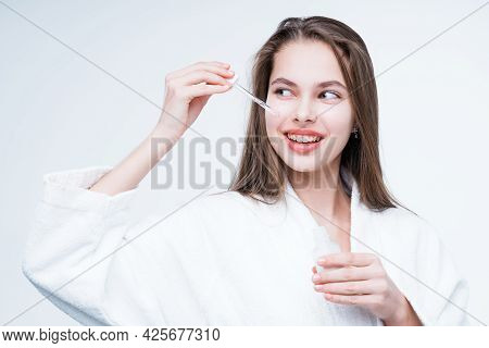 Happy Girl With Long Hair Holding A Dropper In Her Hand And Applying Serum To Her Face Smiling