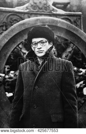 Portrait Of Young Soviet Man With Glasses, In Coat And Hat In The Winter. Vintage Black And White Pa